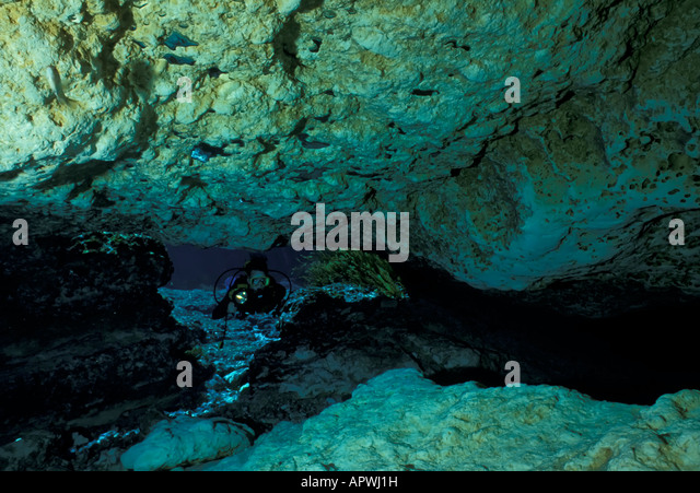 underwater cave diver enters cave mouth adventure - Stock Image
