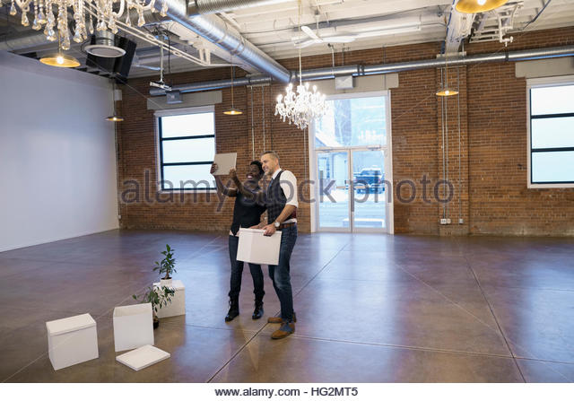 Businessman and businesswoman taking selfie with digital tablet camera in empty new office - Stock Image