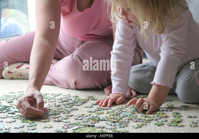 young girl play jigsaw with mother - Stock-Bilder
