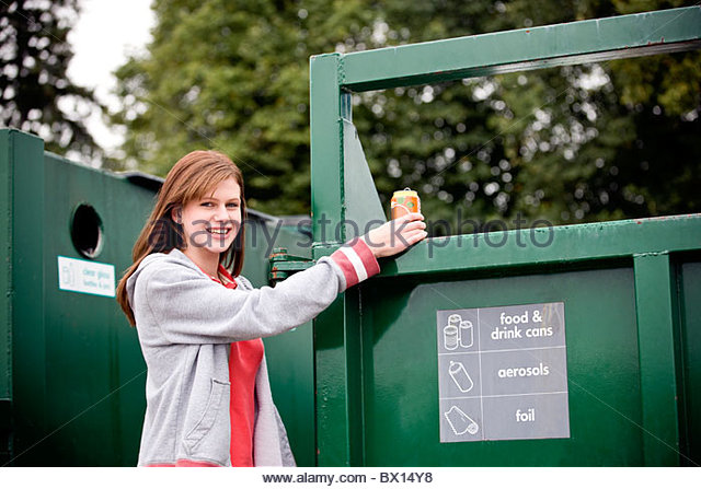 A teenage girl recycling a drink can - Stock Image