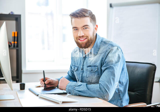 Portrait of happy attractive young designer in jeans shirt working using pen tablet with stylus in office - Stock Image