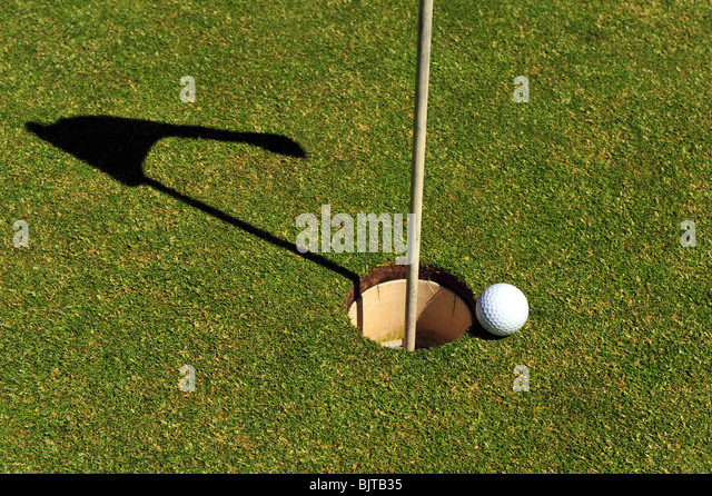 golf ball putting green grass hole flag reflection copy space - Stock Image