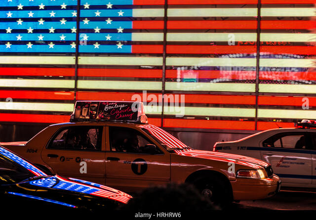 Yellow New York taxi in front of the American flag in Times Square, New York City, United States of America, North - Stock-Bilder