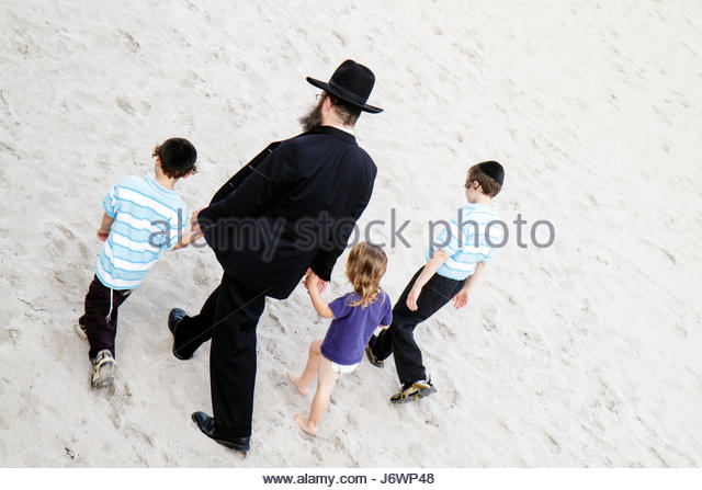 Boca Raton Florida public beach Atlantic Ocean Orthodox Jews family man father children boy girl - Stock Image