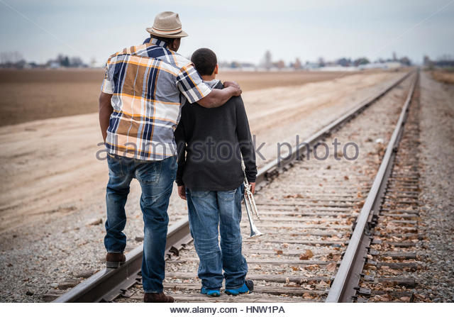 Father and son standing on train track with trumpet - Stock-Bilder