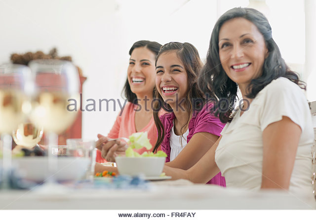 mother and pretty daughters at dinner table - Stock-Bilder