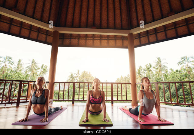 Three women practicing the cobra pose during yoga class at health center. Group of young people doing cobra pose - Stock Image