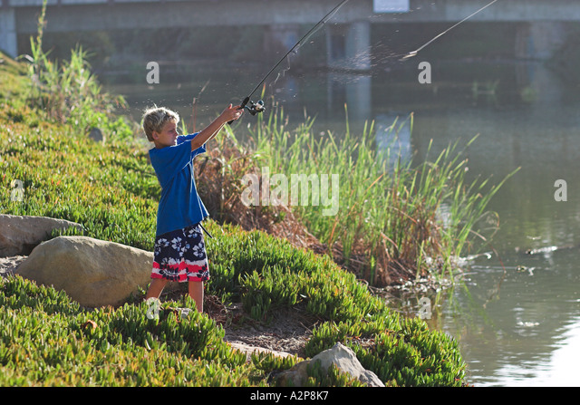 A young boy casts his line into a lake. - Stock Image