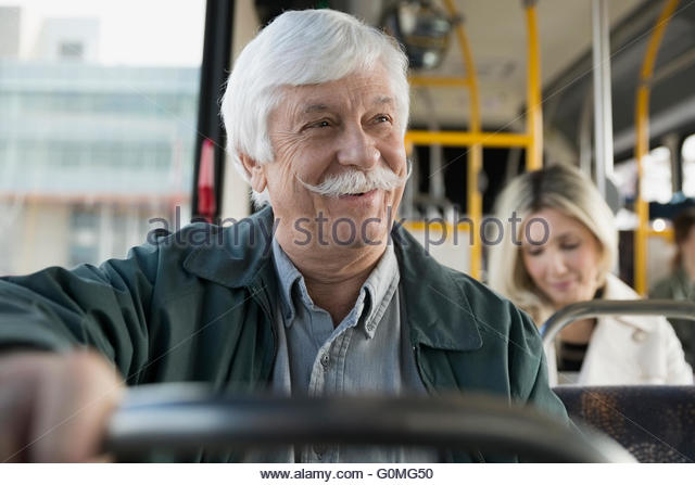 Smiling senior man with mustache riding bus - Stock Image