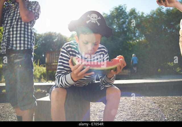 Three young boys having lunch in park - Stock Image