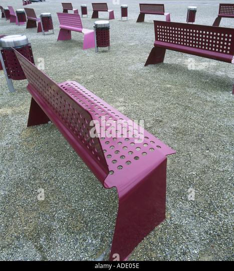 Rows of similar purple metal benches on the ground - Stock Image