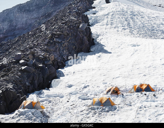 Hikers pitched their tents on a snowy slope on the journey to Mt. Rainier's summit. - Stock Image