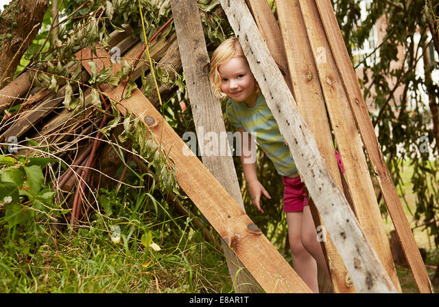 Portrait of girl hiding in garden den - Stock Image