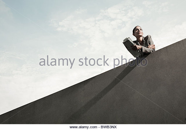 Businesswoman leaning over wall with newspaper, low angle - Stock Image