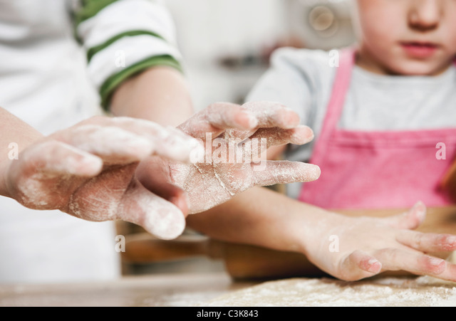 Germany, Cologne, Boy and girl rolling dough on kitchen worktop - Stock-Bilder