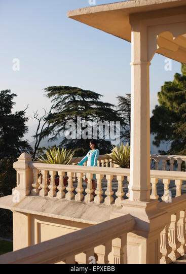A young woman stands on the balcony outside the Vice Regal Suite at Ananda in the Himalayas, The Palace Estate, - Stock Image