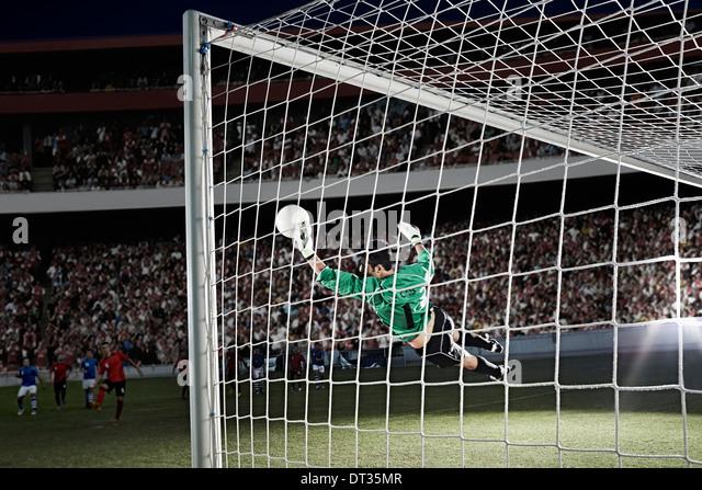 Goalie defending soccer net on field - Stock Image