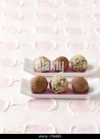 Chocolate truffles on white platters - Stock Image
