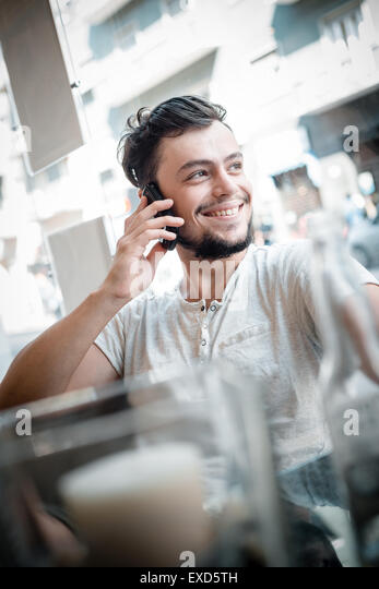 young stylish man at the bar on the phone - Stock Image