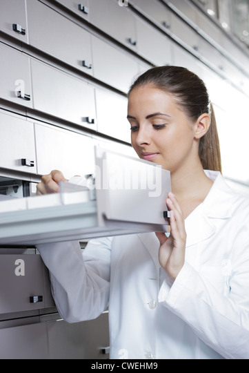 Young woman pharmacist taking medicine from drawer - Stock Image