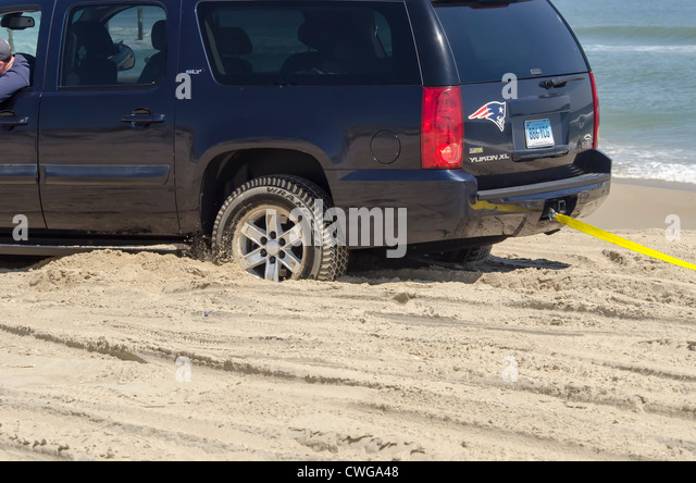Four wheel drive vehicle stuck in sand on beach and being towed out Outer Banks North Carolina - Stock Image