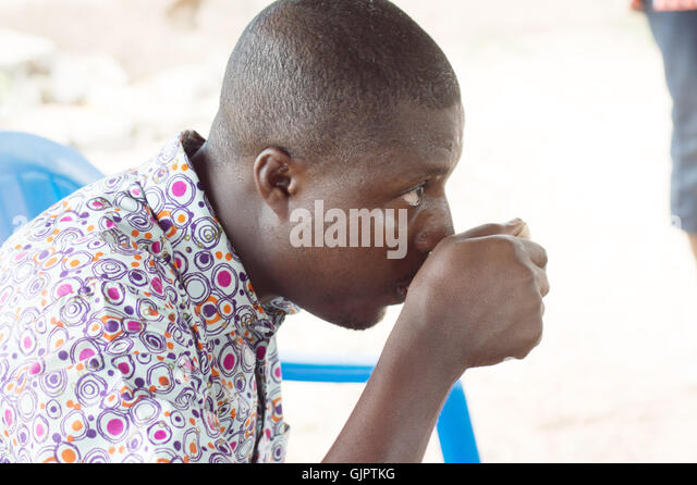 with a traditional cup in hand , this young man refreshes the throat by the palm wine. - Stock-Bilder