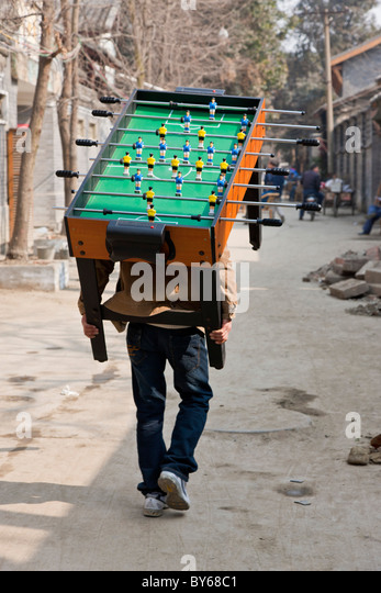 Man carrying Subbuteo football soccer game table on his back through the Hutong, Chengdu, Sichuan Province, China. - Stock Image