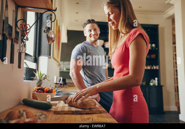 Indoor shot of young man and woman in kitchen during morning. Focus on woman cutting bread, preparing breakfast. - Stock Image