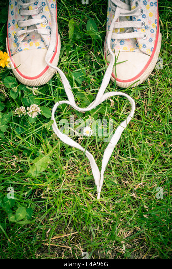 Shoelaces of two sneakers shaping heart on grass - Stock Image