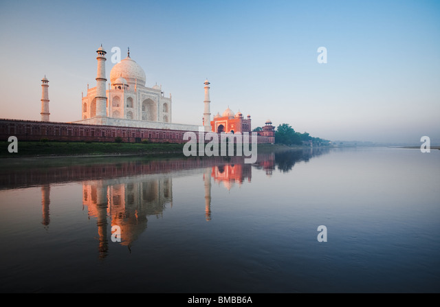 The Taj Mahal glows red at daybreak next to the holy Jamuna river. - Stock Image