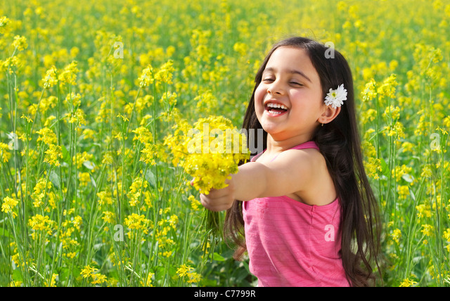 Young girl offering flowers - Stock Image