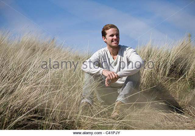 A young man sitting amongst the sand dunes, smiling - Stock Image