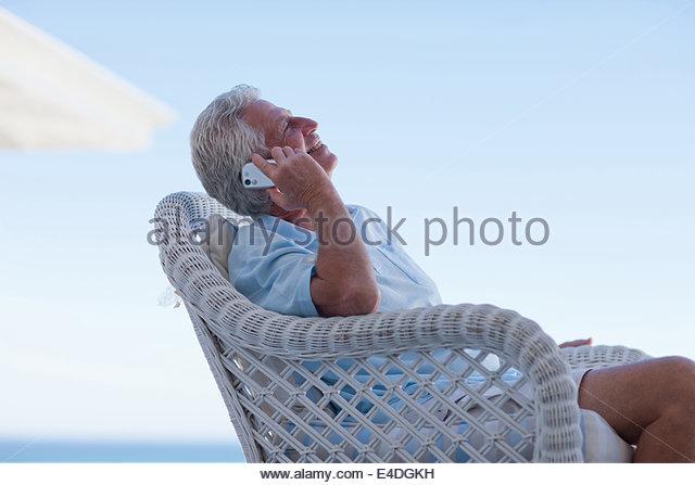 Senior man talking cell phone on beach patio - Stock Image