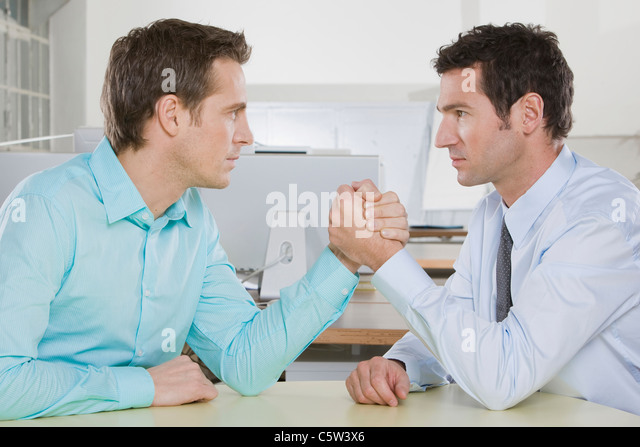 Germany, Munich, two Business men arm wrestling - Stock Image