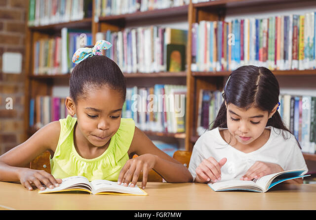 Pupils reading books in the library - Stock Image