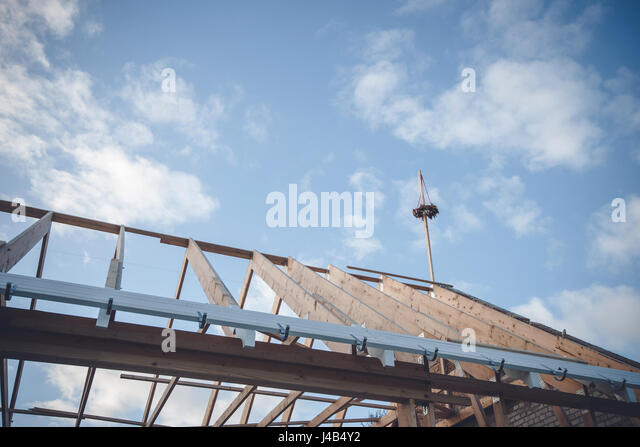 Topping-out ceremony with a wreath on the top of the roof construction on a blue sky - Stock Image