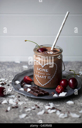 Chocolate coconut smoothie in a jar topped with cherry, dark chocolate, coconut flakes and cacao nibs - Stock Image