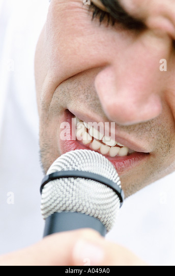 Portrait of young man singing into microphone - Stock-Bilder