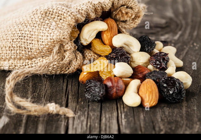 Nuts and dried fruits on wooden background - Stock Image