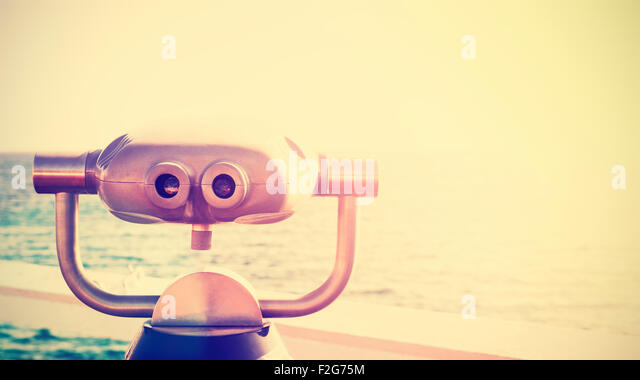 Vintage toned photo of a binocular pointed at horizon, future concept, copy space. - Stock-Bilder