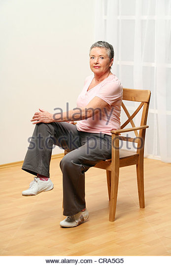 older woman is doing gymnastics on a chair - abdominal muscles - muscularity - senior - Stock Image
