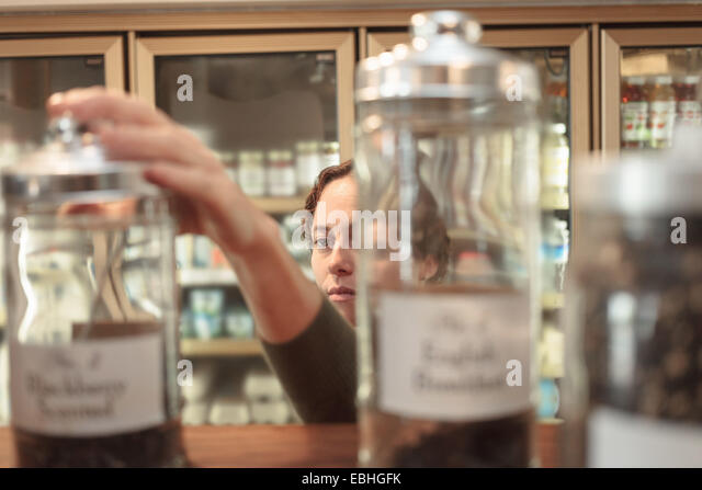 Female customer selecting jar from shelf in country store - Stock Image