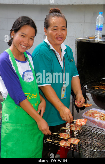 Bangkok Thailand Pathum Wan Rama 1 Road street food vendor Asian woman mother teen girl daughter cooking meat - Stock Image