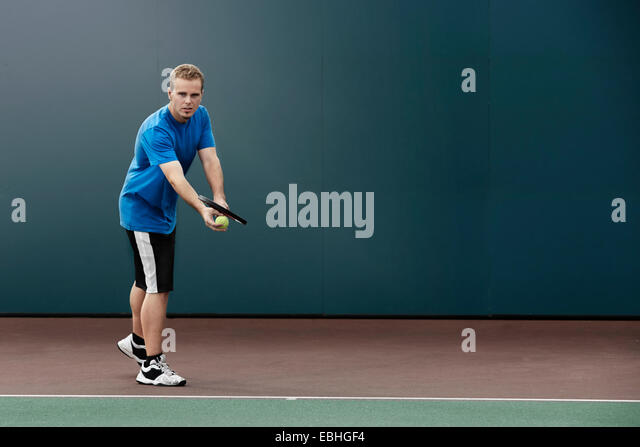 Tennis player about to serve ball in tennis court - Stock Image