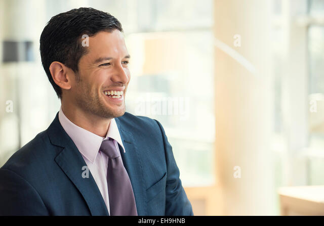 Businessman smiling cheerfully - Stock Image
