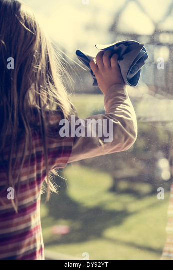 Little girl cleaning window - Stock-Bilder