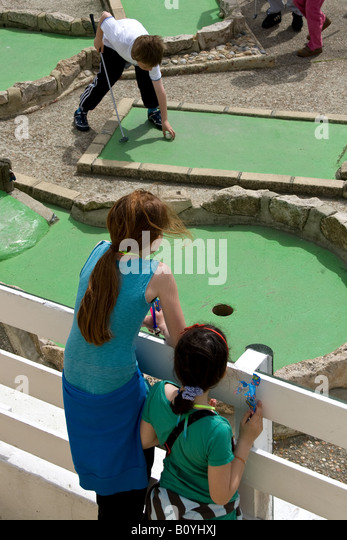 childen playing crazy golf on brighton seafront - Stock Image