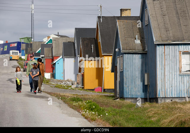 Family walking on the street past a row of houses, Ilulissat, Greenland - Stock-Bilder