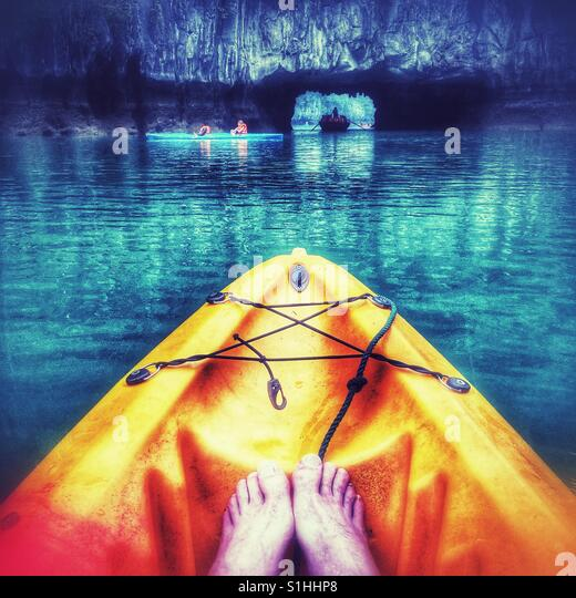 Close-up of  feet at the front of a Kayak in Halong Bay, Vietnam. Luon cave is seen in the background. - Stock Image