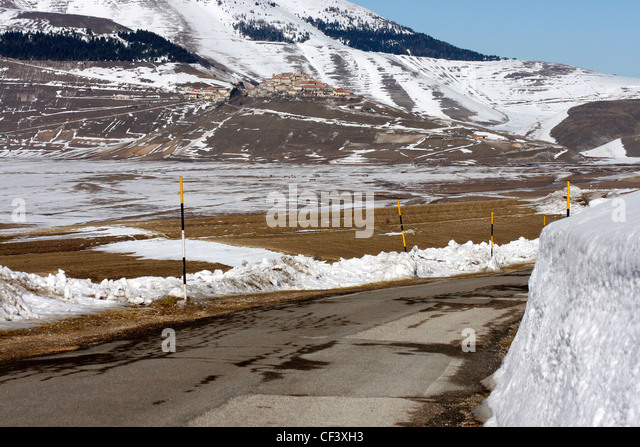 Winter snow view of Castelluccio  across the Piano Grande with depth of snow  pole indicators along the road. - Stock Image